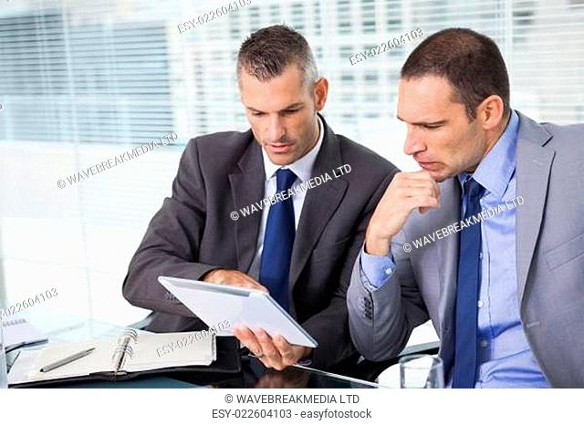 Concentrated businessmen analyzing documents on their tablet