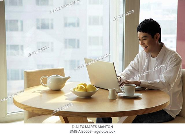 Young man sitting at a table working on a laptop computer