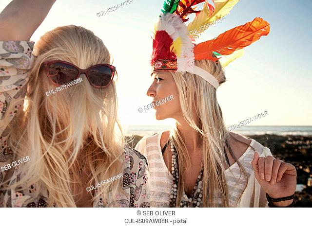 Young women wearing feather headdress and sunglasses with hair covering face