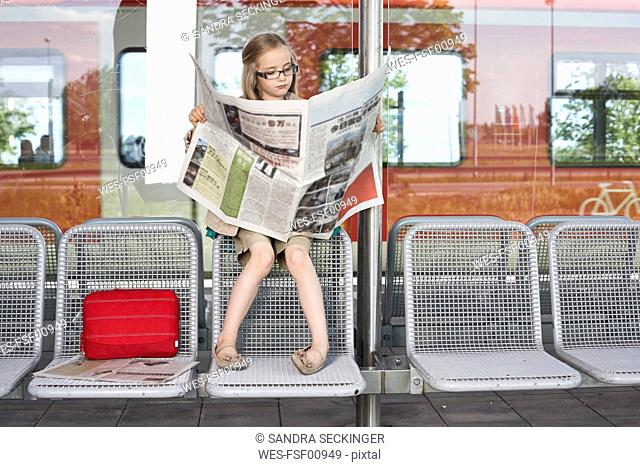 Portrait of little girl sitting at platform reading newspaper