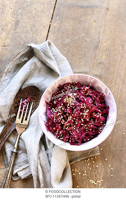 Small bowl of red cabbage salad with sesame on wooden table