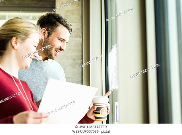 Two colleagues at office window looking at papers