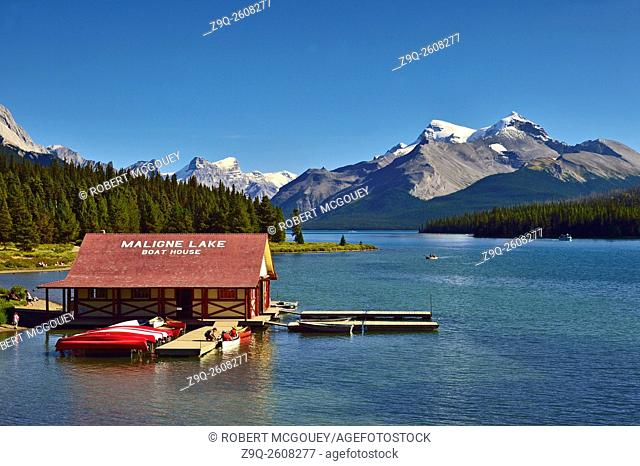 A landscape view of the boat house on Maline Lake in Jasper National Park Alberta, Canada with snow-capped rocky mountians in the background
