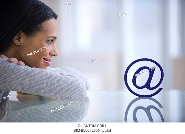 Mixed race woman staring at email symbol