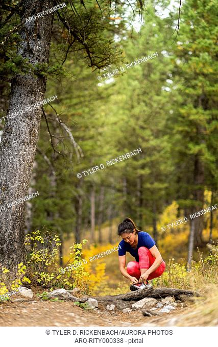 Young athletic woman tying shoelaces while trail running in forest
