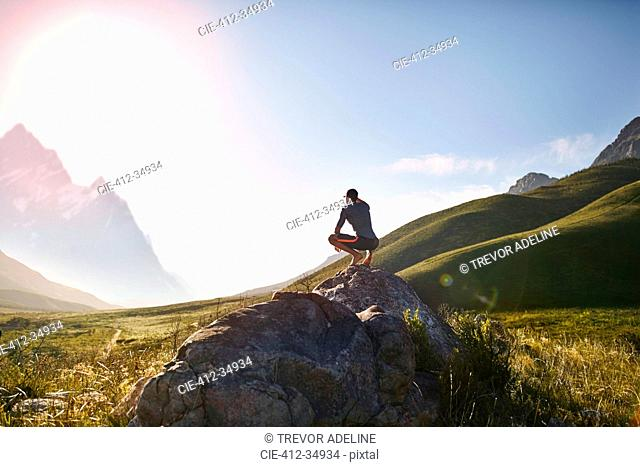 Young man crouching on rock, looking at sunny,r emote mountain view
