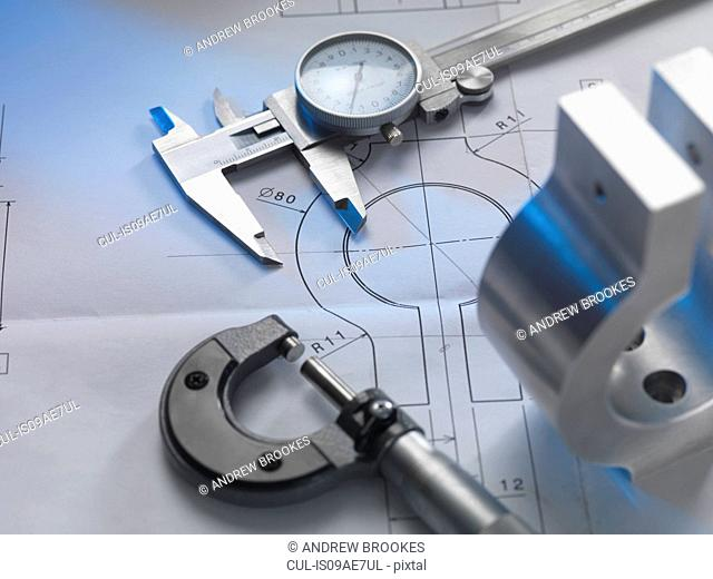 Engineering drawing with product, micrometer and calipers