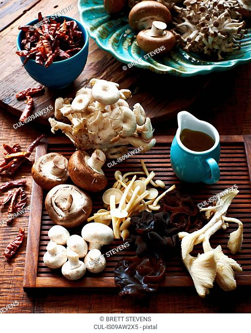 High angle view of various mushrooms on wooden board and dried chillis in bowl
