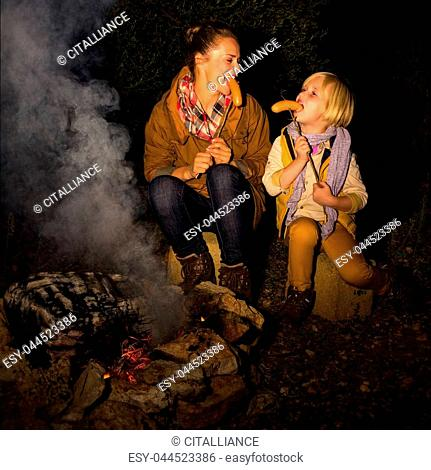 Into the wild. happy young mother and daughter tourists by a campfire eating grilled sausages