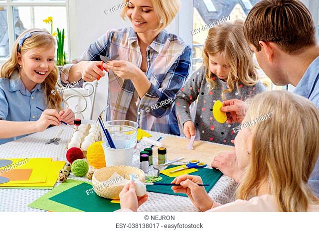Cheerful family having fun painting and decorating easter eggs