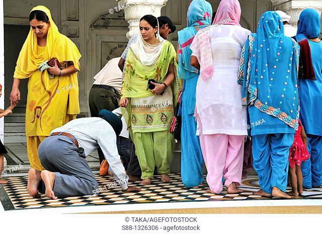 Sikh pilgrims praying in the Golden Temple complex, Punjab Amritsar India