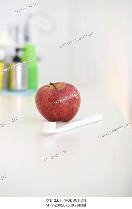 Apple and toothbrushes on table, Munich, Bavaria, Germany