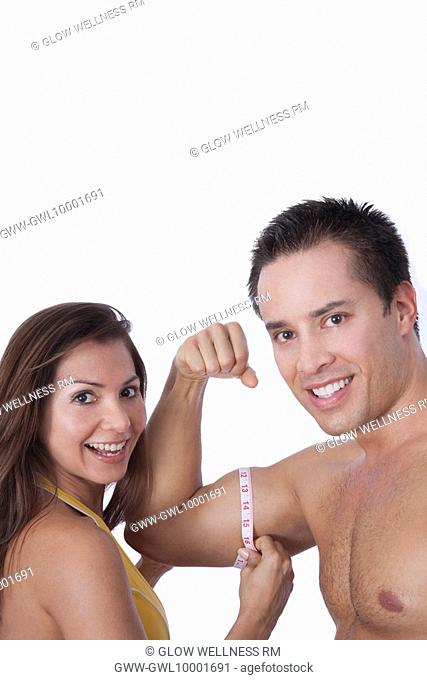 Woman measuring biceps of a man with a tape measure