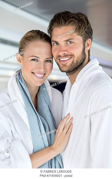 Portrait of a smiling couple in bathrobes at spa