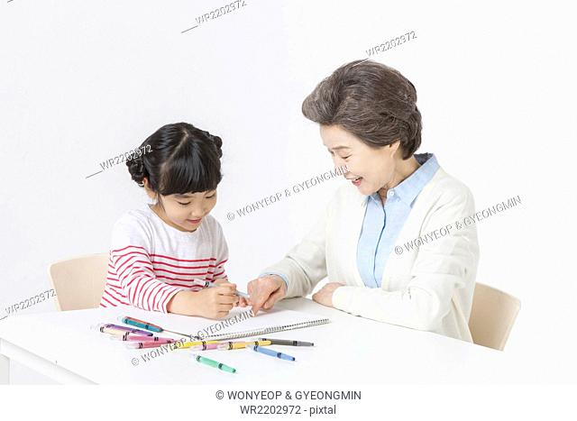 Young girl drawing on sketch pad with color pencils and her grandmother seated right next to her looking down and pointing the drawing with her finger