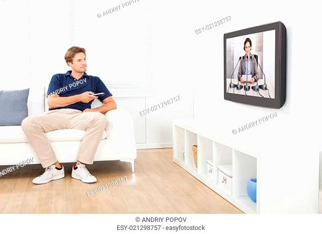 Man Watching News On TV At Home