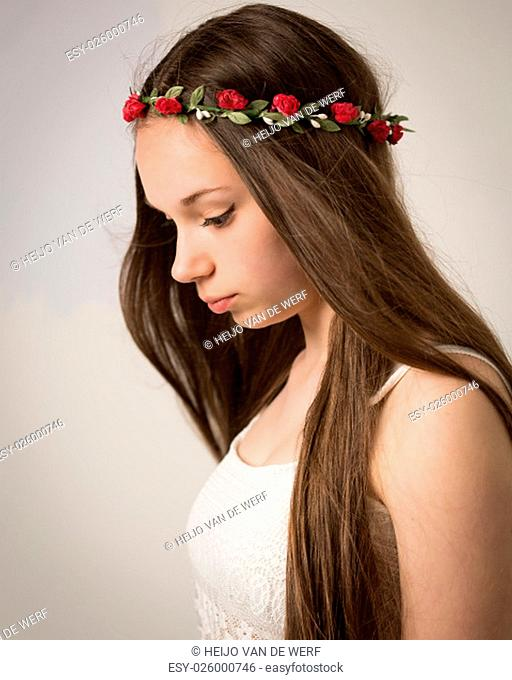 Studio portrait of a beautiful teenage hippie girl with extremely long brown hair wearing a lace white top and a flower wreath isolated against a grey...