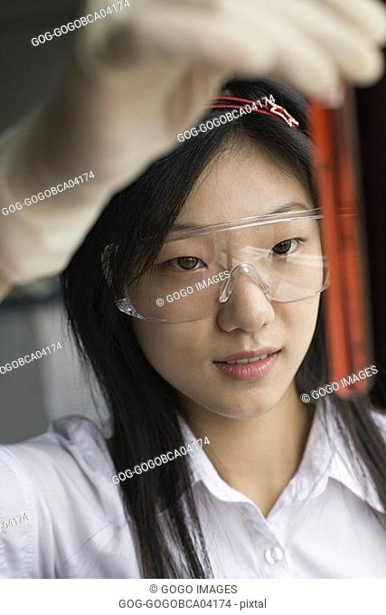 Female student examining the contents of a test tube