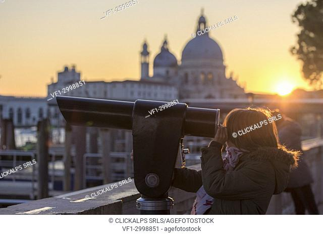 Little girl looking trough the telescope the Grand Canal, in the background the basilica di Santa Maria della Salute, Saint Mary of Health at sunset, Venice