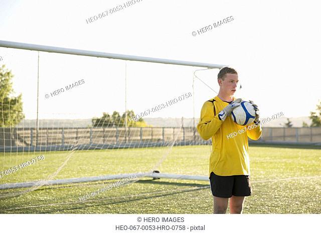Soccer goalie holding ball in front of net