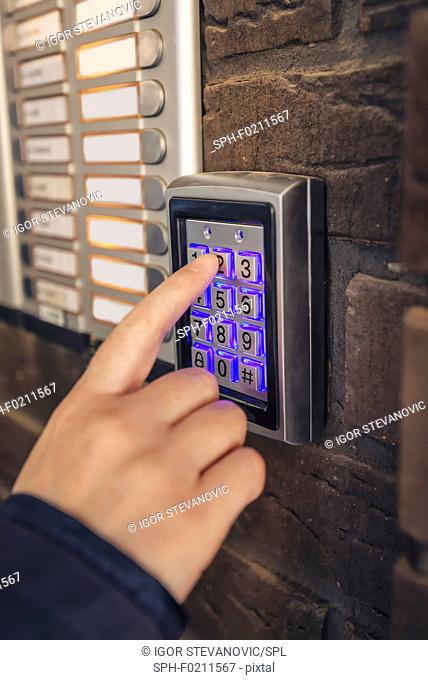 Woman entering passcode on security keypad