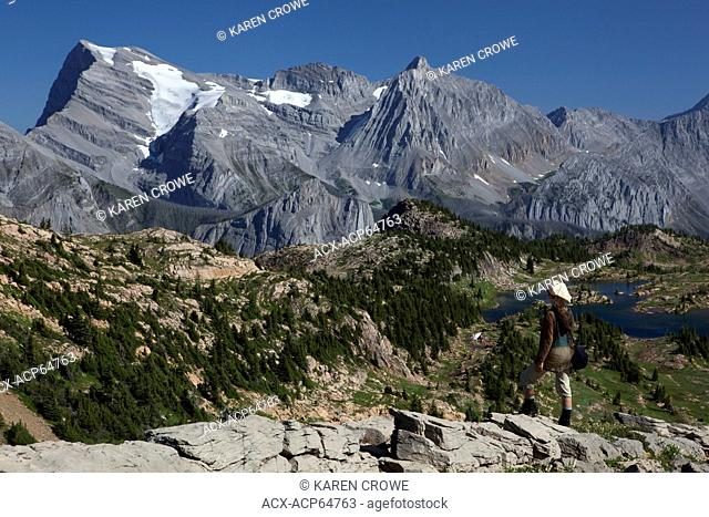 Hiker above Limestone Lakes, looking at Mount Abruzzi and Mount Lancaster, Height of the Rockies Provincial Park, British Columbia, Canada