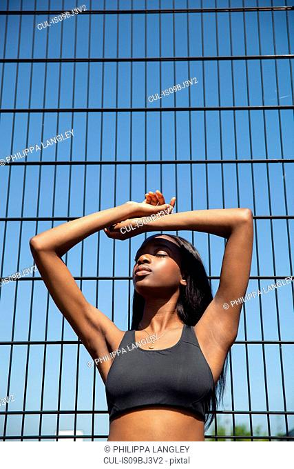 Young woman leaning against wire fence