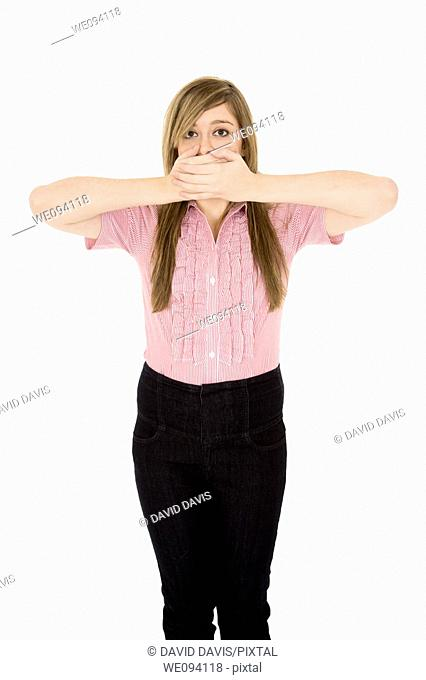 Caucasian teenager displaying some attitude with the Speak No Evil hands over mouth