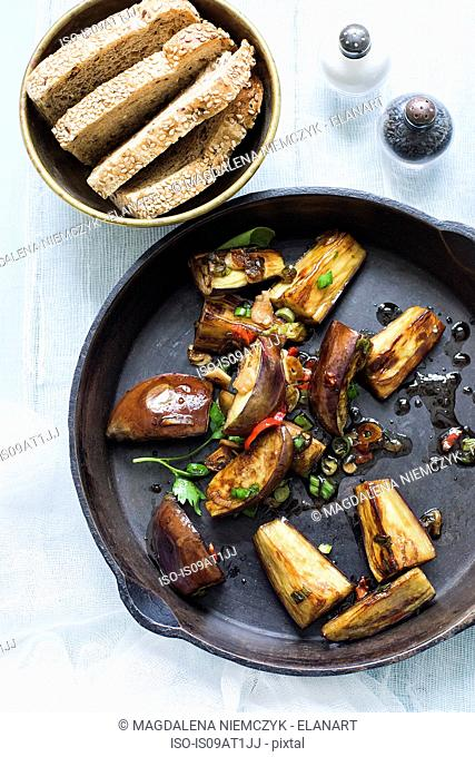 Still life of fried aubergines and herbs in frying pan