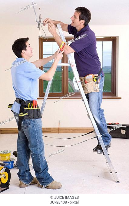 Electricians wiring ceiling