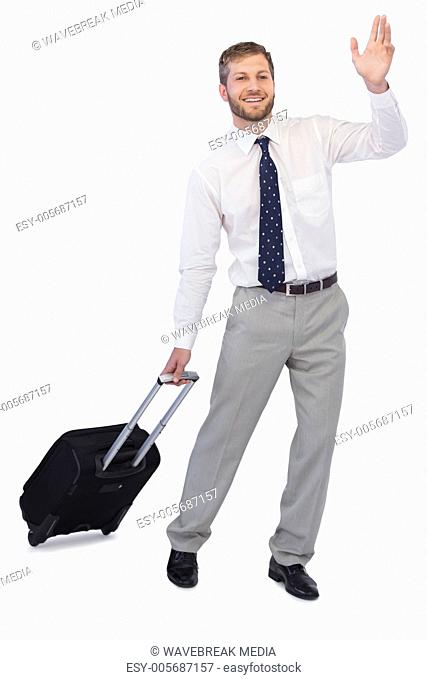 Handsome businessman with suitcase waving