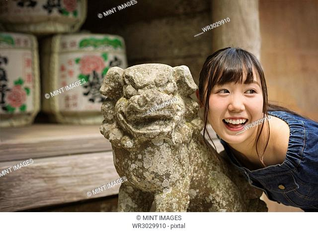 Young woman wearing blue dress standing next to stone sculpture of lion at Shinto Sakurai Shrine, Fukuoka, Japan