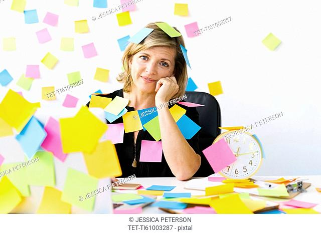 Portrait of Mature woman at office covered with adhesive notes