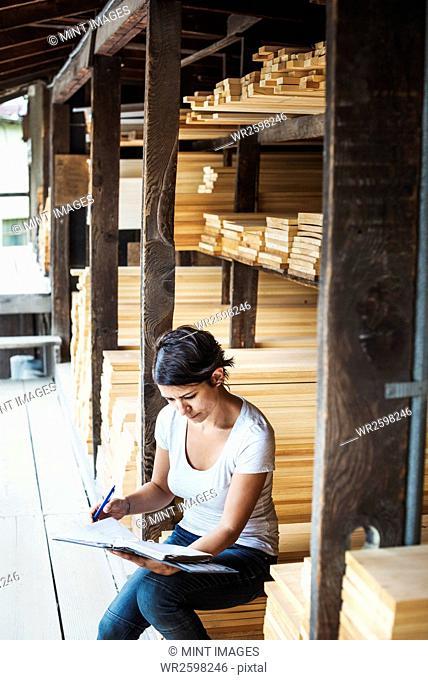 Woman sitting in a lumber yard, holding a folder