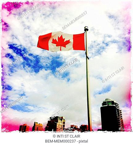 Canadian flag flying on top of flag pole