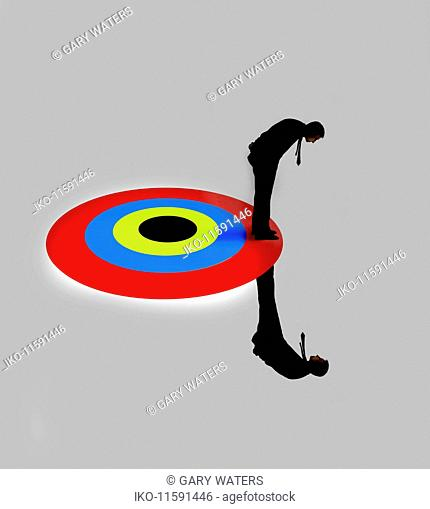 Businessman standing above and below target