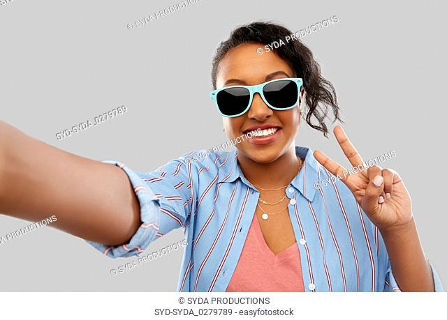 african american woman in sunglasses taking selfie