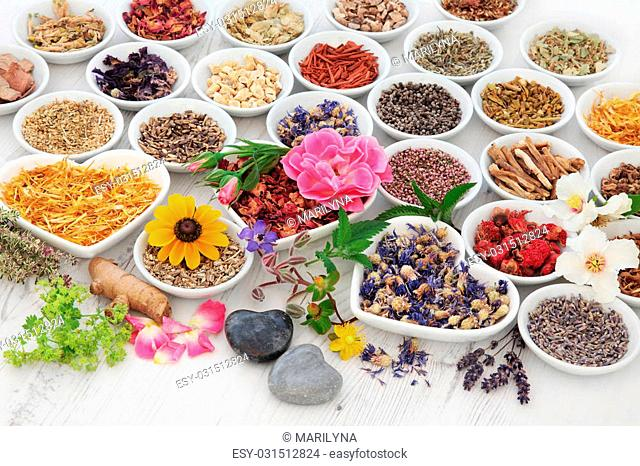 Large herb and flower selection used in herbal medicine in porcelain bowls over distressed wooden background