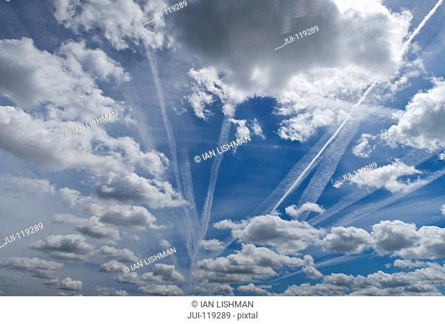Blue sky, fluffy white clouds and jet trails