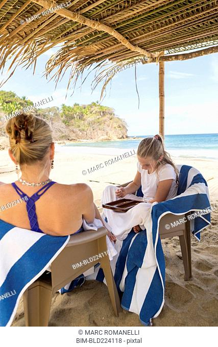 Caucasian mother and daughter playing backgammon at beach