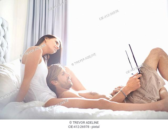 Casual couple relaxing with laptop on bed