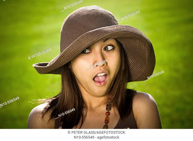 Young Spanish/Asian woman, wearing a hat, posing at a park