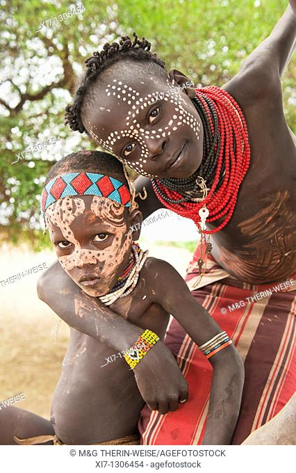 Two Karo children with face paintings in a tree, Omo river valley, Southern Ethiopia