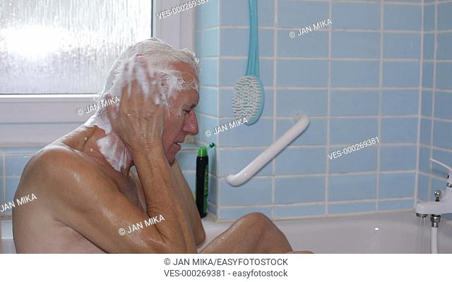 Senior man in bath washing his hair with shampoo