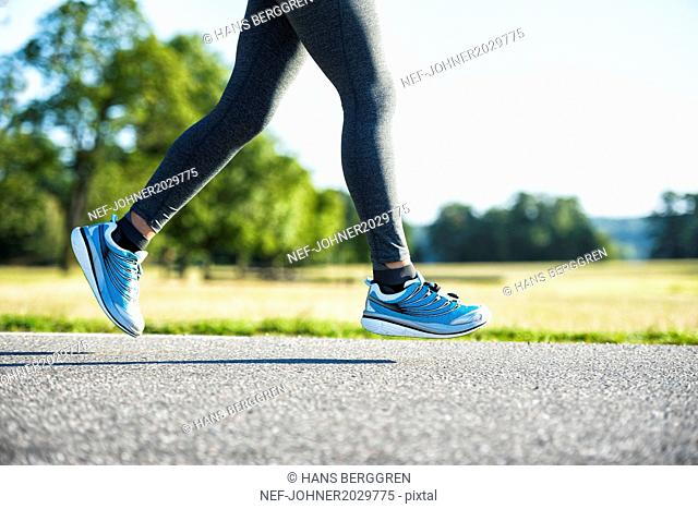 Woman jogging on country road