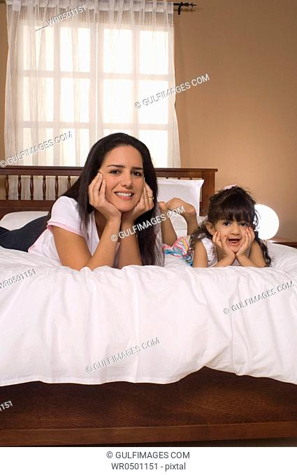 Daughter 3-4 with mother lying on bed