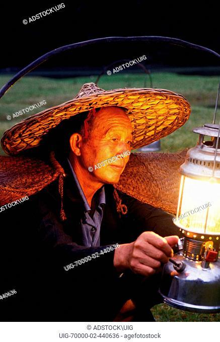Li River cormorant fisherman lighting lantern on his bamboo raft at Xingping China near Guilin