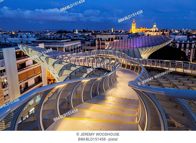 Curving footbridge over Seville cityscape, Andalusia, Spain