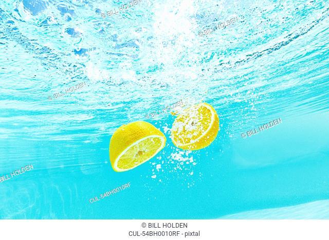 Sliced lemon splashing into water