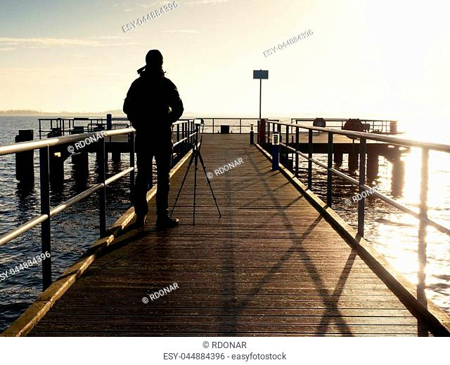 Alone artist on wooden sea bridge. Photographer with with mirror camera and tripod at end of pier board. Fall foggy misty sunrise above smooth sea